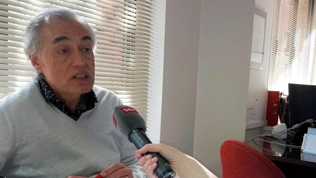 Der Arzt und Gewerkschaftssekretär Josep Maria Puig spricht mit SRF-Reporterin Melanie Pfändler. Sie hält ein Mikrofon mit SRF-Aufschrift. Er hat graue Haare, einen dunklen Teint und trägt einen grauen Pullover mit einem blauen Hemd darunter.