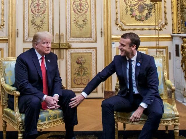 Trump und Macron sitzend.