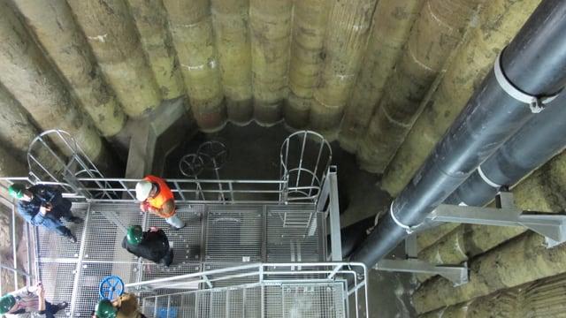 Blick von oben in den tiefen Schacht, an den Wänden sieht man kleine Röhren die als Wandverkleidung dienen und aus Beton sind. An der einen Wandseite sind die beiden Abwasserrohre angebracht.