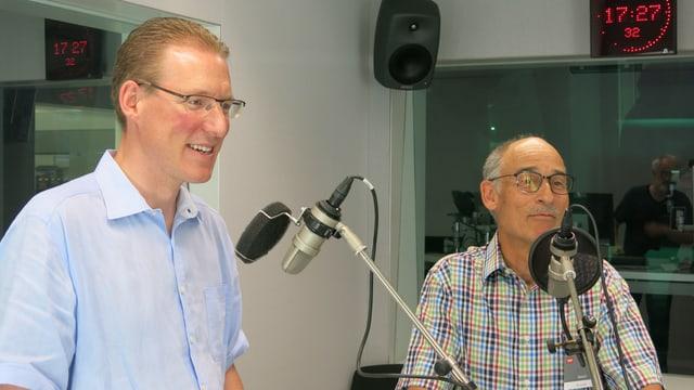 Zwei Männer vor ihren Mikrofonen.