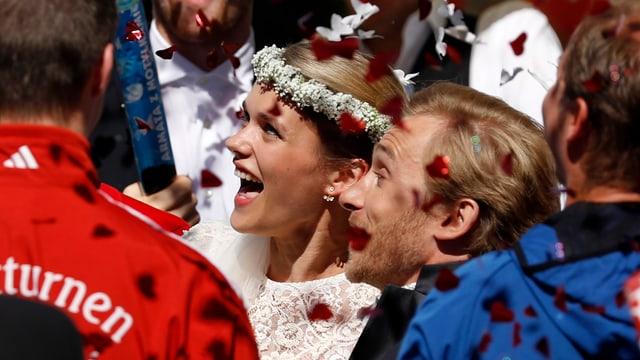 Rosenblätter fliegen, dazwischen strahlendes Brautpaar