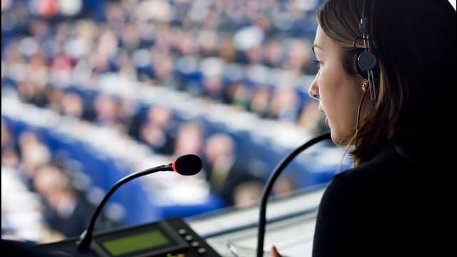 Eine Übersetzerin mit Kopfhörer spricht in ein Mikrofon während einer Debatte.