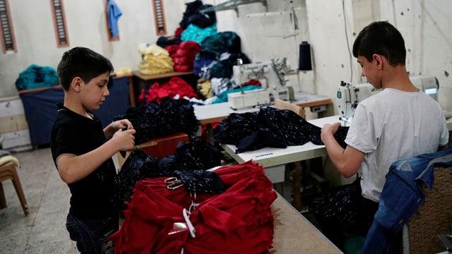 Zwei Jungen stehen in einer Textilfabirk an einer Nähmaschine und neben einem Stapel Textilien.