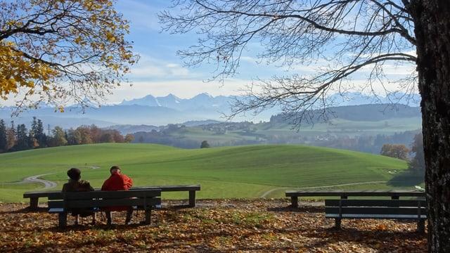 Wanderer sitzen auf einer Aussichtsbank auf dem Berner Hausberg Gurten.