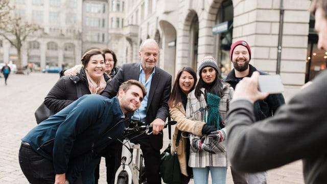Stadtrat Filippo Leutenegger posiert für ein Foto mit Touristinnen und Touristen.