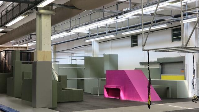 Eine Fabrikhalle mit Betonelementen, eines davon pink angemalt.
