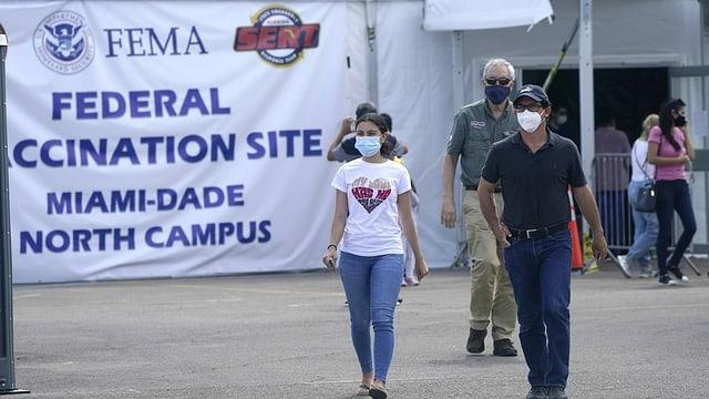 Personen gehen aus einem Impfzentrum in Miami.