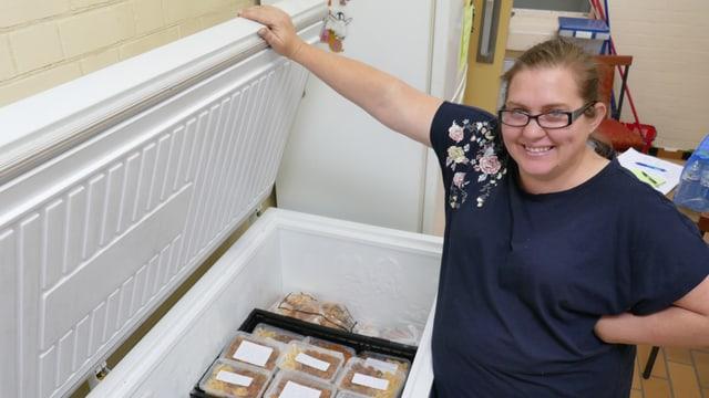 Frau hebt Deckel von Tiefkühltruhe. Im Innern sind tiefgekühlte Fertig-Mahlzeiten.