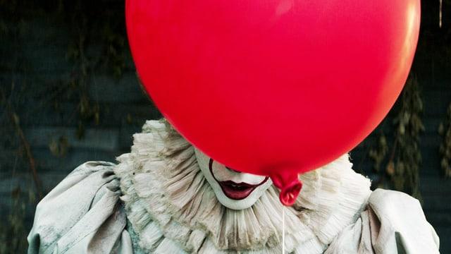 Ein Ballon verbirgt ein Clown-Gesicht.