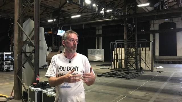 Ein Mann steht in einer leeren Industriehalle.