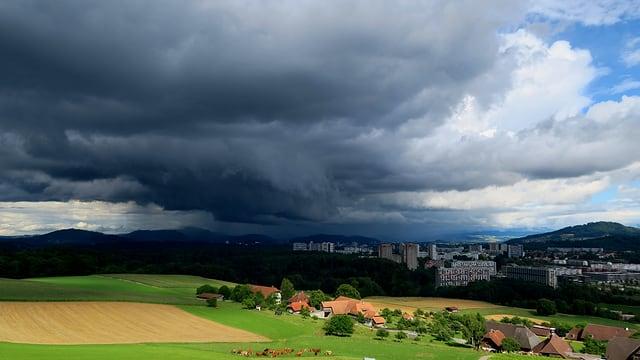 Blick von Frauenkappelen Richtung Bern. Dort ist es schwarz durch eine mächtige Gewitterwolke.