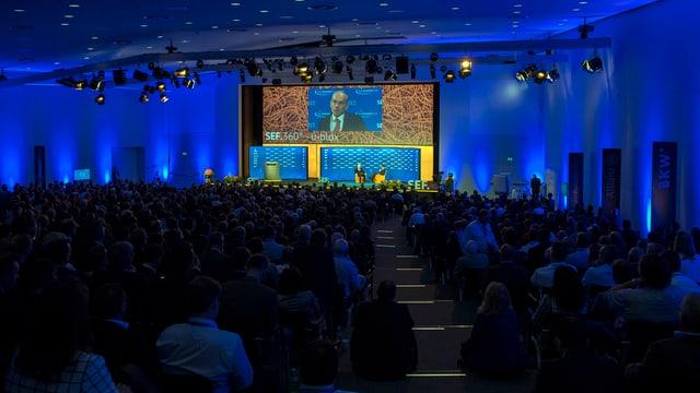 Ein voller Saal, zuvorderst eine Videowand.