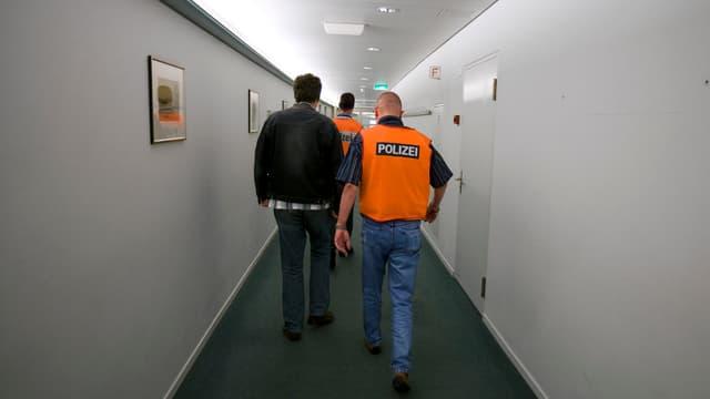 Polizisten begleiten einen auszuschaffenden Mann durch einen Korridor.