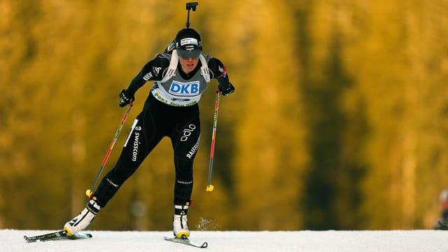 Lena Häcki mit Gewehr auf dem Rücken am Langlaufen.