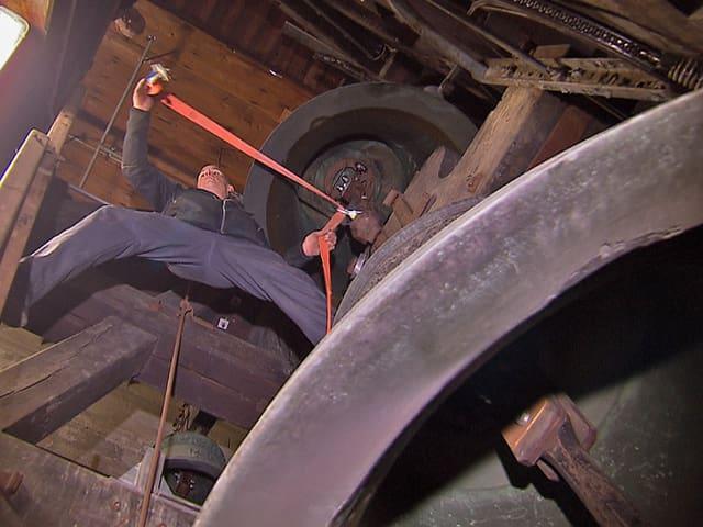 Ein Mann befestigt im Glockenturm einen Glockenklöppel.