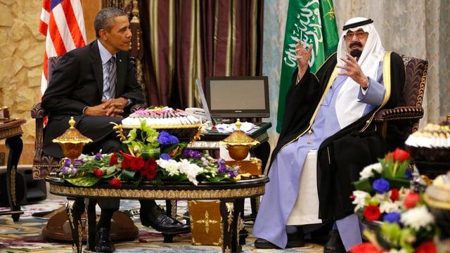 Barack Obama und König Abdullah sitzen bei Tisch.