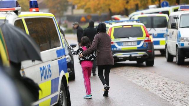 Autos da polizia ed ina mamma cun in uffant che van.