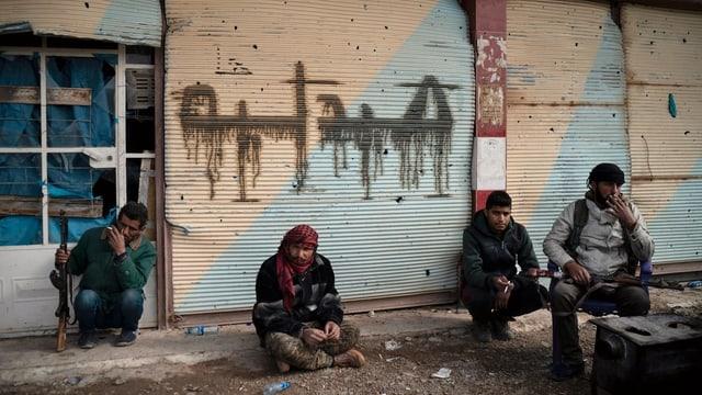 Vier sitzende Männer mit Waffen pausieren vor einem Gebäude