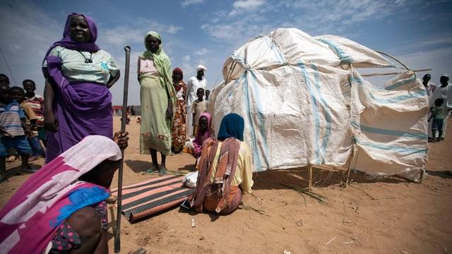 Afrikanische Frauen bauen ein Zelt auf