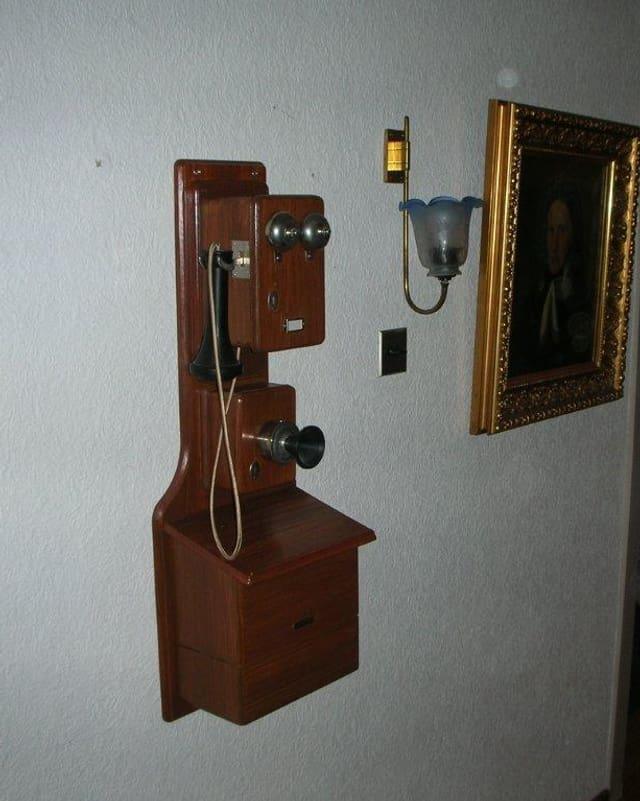 Ein altes Telefon hängt an der Wand.