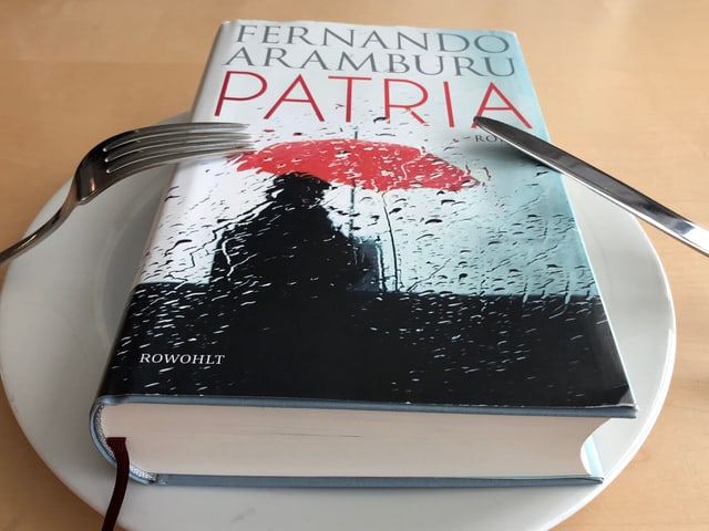 «Patria» liegt auf einem weissen Teller, Messer und Gabel daneben.