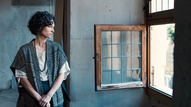 Eine Frau blickt nachdenklich durch ein geöffnetes Fenster.