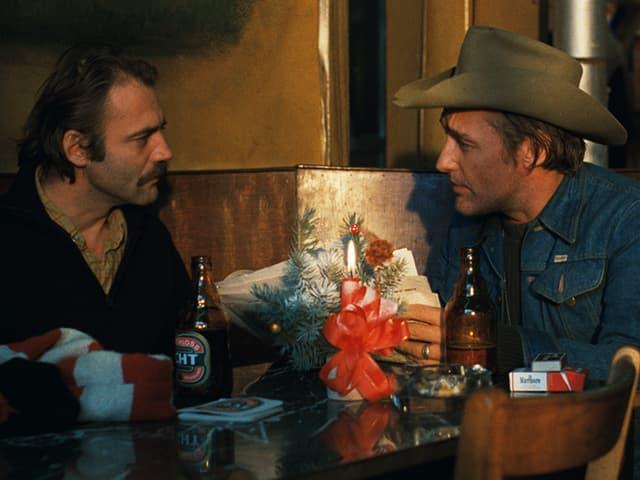 Zwei Männer stehen sich gegenüber, einer raucht eine Zigarette
