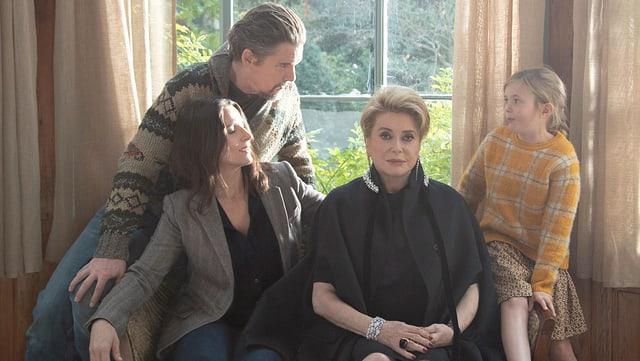 Die Filmfamilie sitzt auf einem Sofa. In der Mitte sind Catherine Deneuve.