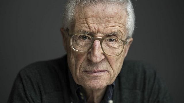 Älterer Mann mit grauen Haaren und Brille schaut direkt in die Kamera