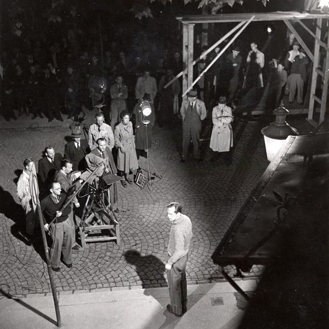 Nachtszene aussen, ein Schauspieler wird beleuchtet. Vor ihm stehen die Kamera und der Tonmann.