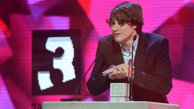 Ein junger Mann mit Anzug und glattem Haar, das über Stirn und Augen fällt, steht an einem Pult mit zwei Mikrofonen. Vor ihm steht ein kleiner Betonklotz mit der Inschrift Swiss Music Awards. Im Hintergrund ist das Zeichen von Radio SRF 3 zu sehen.