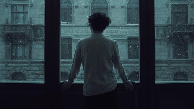 Mann vor Fenster Symbolbild
