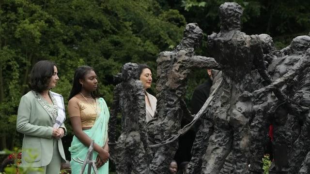 Femke Halsema steht neben zwei Frauen beim nationalen Sklavendenkmal in Amsterdam.