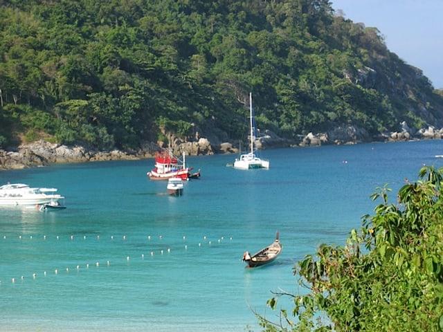 Eine idyllische Bucht mit türkisblauem Wasser und mehreren Booten.