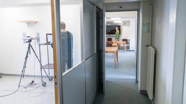 Gerät und eine Person im einen Raum, andere Person in anderem Raum.