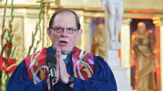 Pfarrer in blauem Talar in einer Kirche