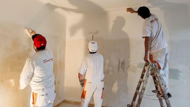 Drei Maler a7uf einer Baustelle, die einen Innenraum malen. Die Männer sieht man von hinten.