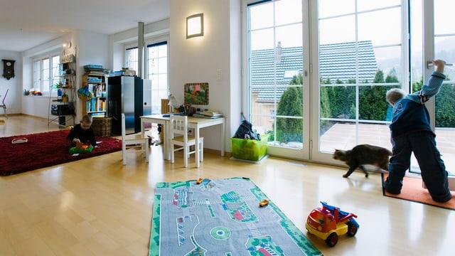 Kind in moderner Wohnung öffnet Fenster und lässt Katze hinein.