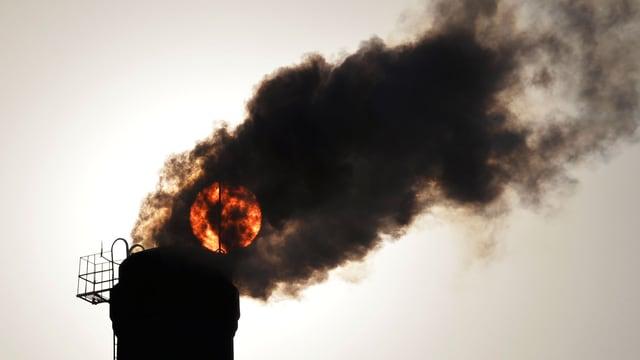 Kamin mit schwarzer Rauchwolke. Dahinter schimmert die Abendsonne.