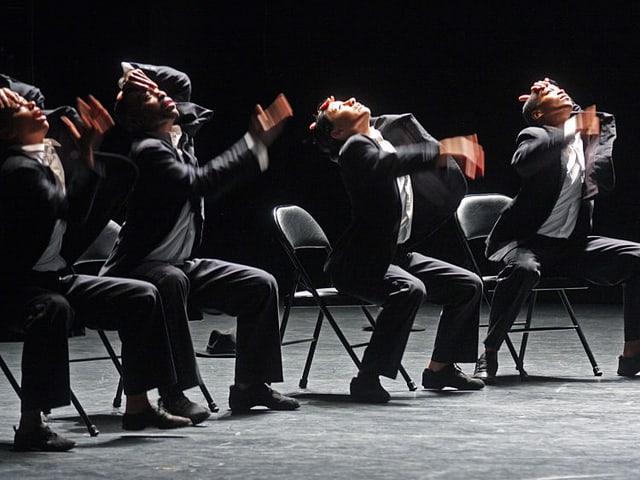 Männer in Anzügen sitzen auf Stühlen und wirbeln mit den Oberkörpern.