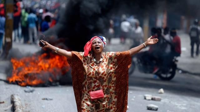 Eine Demonstrantin skandiert Parolen, Reifen brennen im Hintergrund