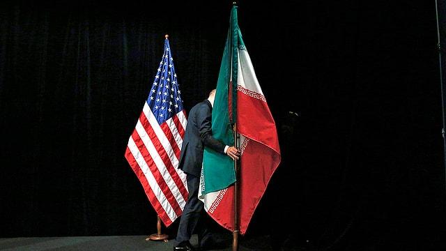 Ein Mann entfernt die Flaggen der USA und jene des Irans von einem Gesprächspodium.