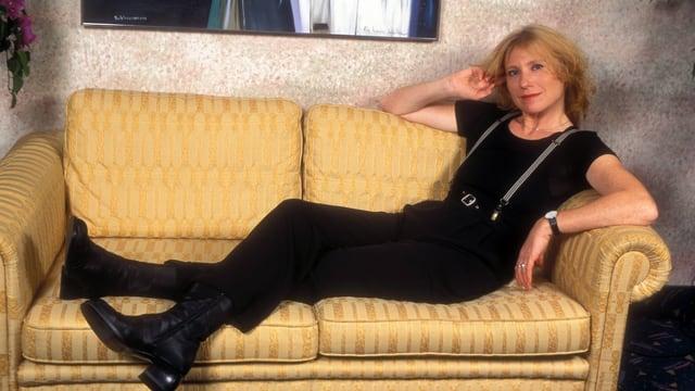 Maren Kroymann posiert auf einem Sofa.
