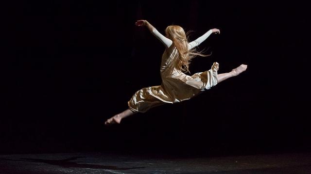 Eine Tänzerin in einem langen Rock springt in die Luft und macht einen Spagat.