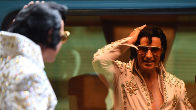 EIn Double von Elvis Presley schaut sich im Spiegel an und fährt sich durch die Haare.