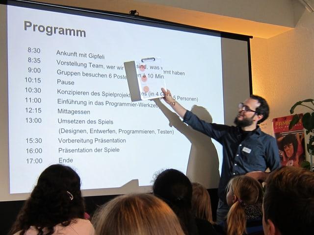 Ein Mann zeigt mit einem Notizblock ein vom Hellraumprojektor auf eine Leinwand projiziertes Tagesprogramm.