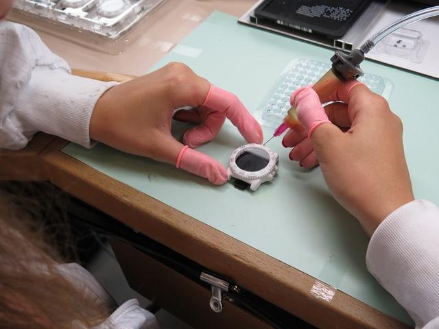 Eine Frau arbeitet mit Gummihandschuhen an einer Uhr