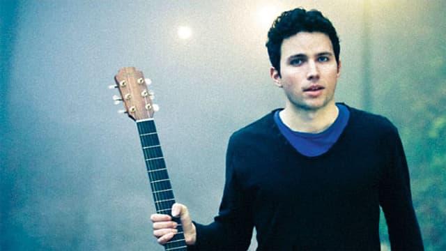Levin auf dem Cover seiner neuen CD für «Between The Lights». Er trägt eine blaues T-Shirt unter einem schwarzen Pullover und hält in der rechten Hand eine Gitarre.