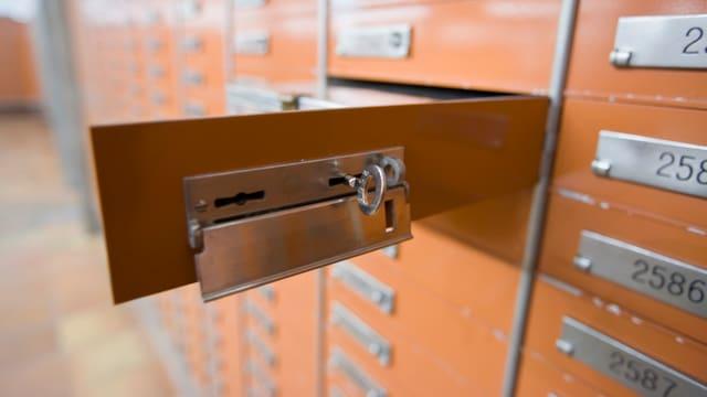 Ein offenes braunfarbenes Schliessfach mit Schlüssel.