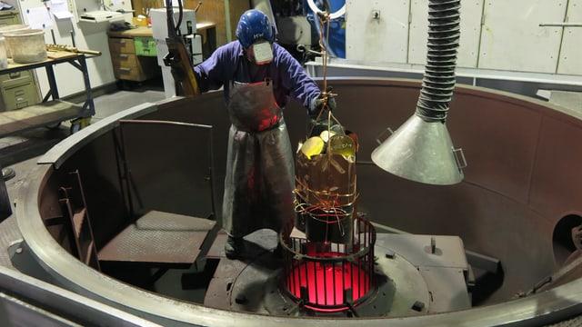 Ein Giesser der Schmelzmetall füllt den Vakuum-Ofen in Gurtnellen mit frischem Kupfer.